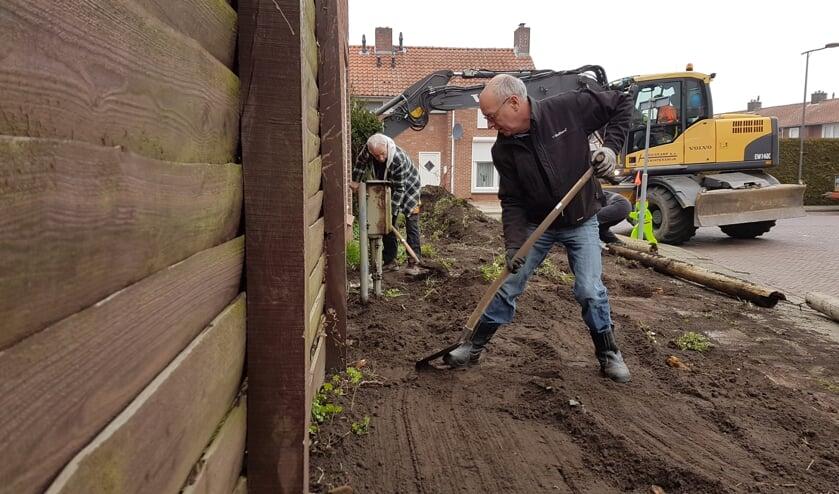 Vrijwilligers van Present en Loonwerkersbedrijf Huiskamp maken een van de tuinen schoon