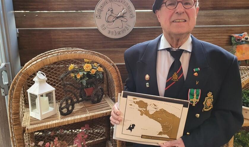 <p>Antoon te Brake trots op zijn decoraties en baret, met de landkaart van voormalig Nederlands Nieuw Guinea. Foto: Henri Walterbos</p>