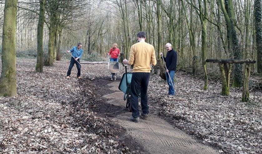 <p>Vrijwilligers leggen een semiverhard pad aan in het dorpsbos van Steenderen, geschikt voor rolstoelen, kinderwagens et cetera. Foto: Karin van Heijst</p>