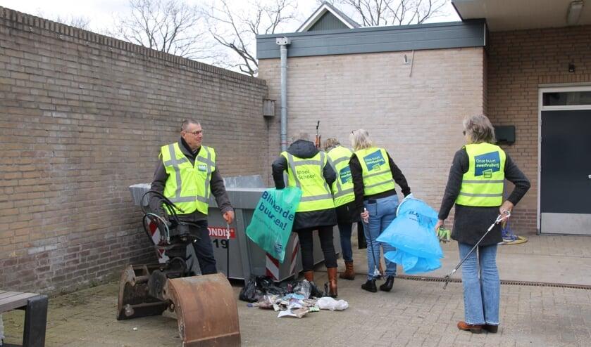 <p>Gerard en een aantal leden van de groep Schoon Oost Gelre bij de afvalcontainer achter het gemeentehuis. Foto: Annek&eacute;e Cuppers</p>