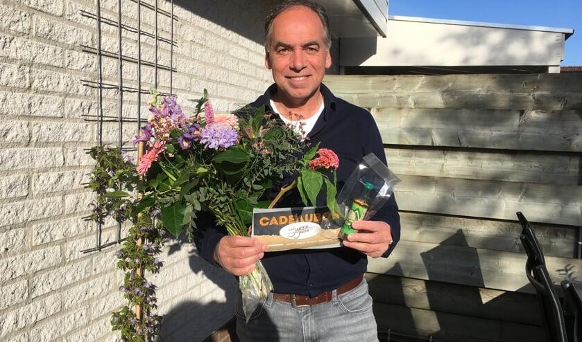 <p>Paul Mokkink neemt bloemen en dinerbon Eetcaf&eacute; Jansen & Jansen in ontvangst. Foto: PR HLTC Het Elderink</p>