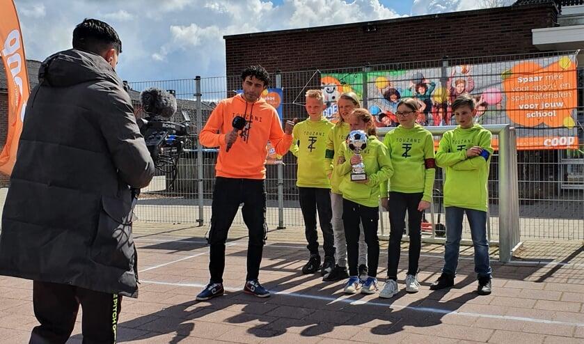 <p>Winnaars zijn Team Groen, zij zijn De Street Captains van De Dorpsschool. Touzani feliciteert hen in de camera met het winnen van de grote beker. Foto: Alice Rouwhorst</p>