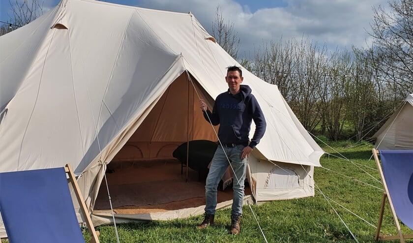 <p>Dinand Garritsen bij het type tent The Boss, vierpersoons op zijn farmglamping De Scheurwei. Foto: Alice Rouwhorst</p>