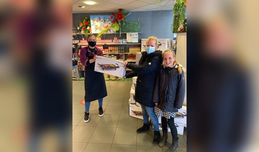 <p>Roos Wiggers van Keurslager Kamperman overhandigt de bakplaat aan een van de winnaars: Istry Tangelder. Foto: PR</p>