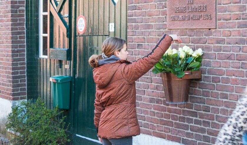<p>Een leerling plaatst haar roos in de emmer. Foto: Henk Derksen</p>