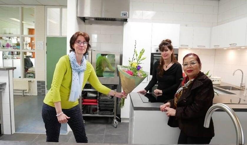 <p>Directeur-bestuurder Jorinde Klungers (Perspectief Zutphen) overhandigt bloemen aan vrijwilliger Nina Lalenoh en sociaal beheerder Greet Zweers in de nieuwe keuken van buurthuis De Uitwijk. Foto: PR</p>