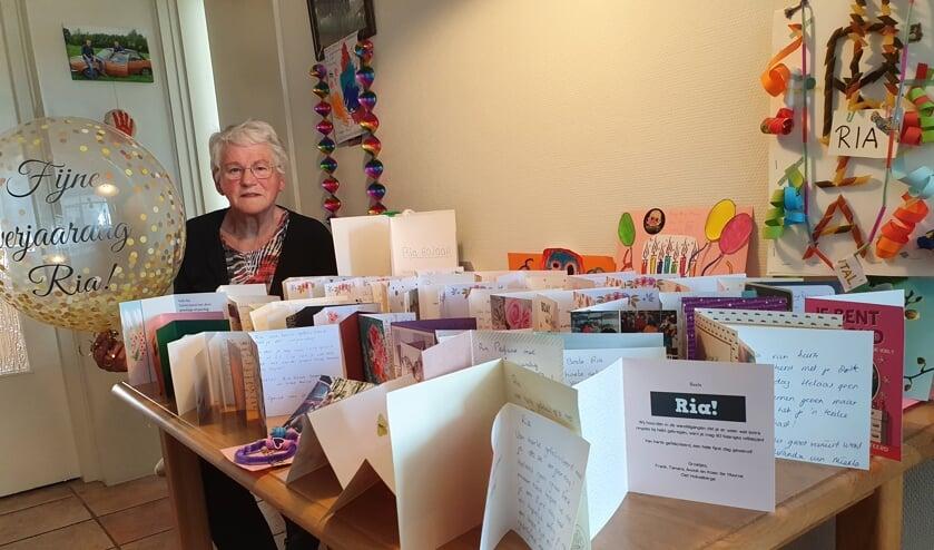 <p>Ria aan de keukentafel vol verjaardagskaarten. Foto: Henri Walterbos</p>