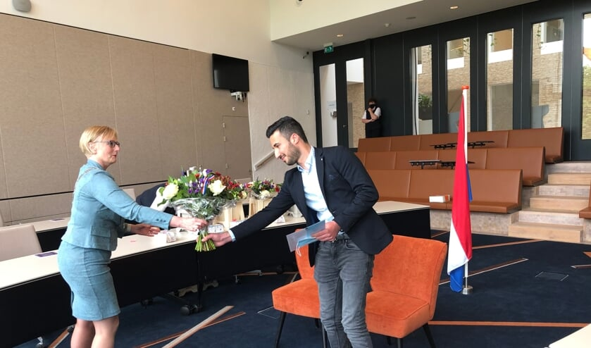 <p>Shervan kreeg uit handen van burgemeester Marianne Besselink zijn papieren voor het Nederlanderschap en bloemen. Foto: PR</p>