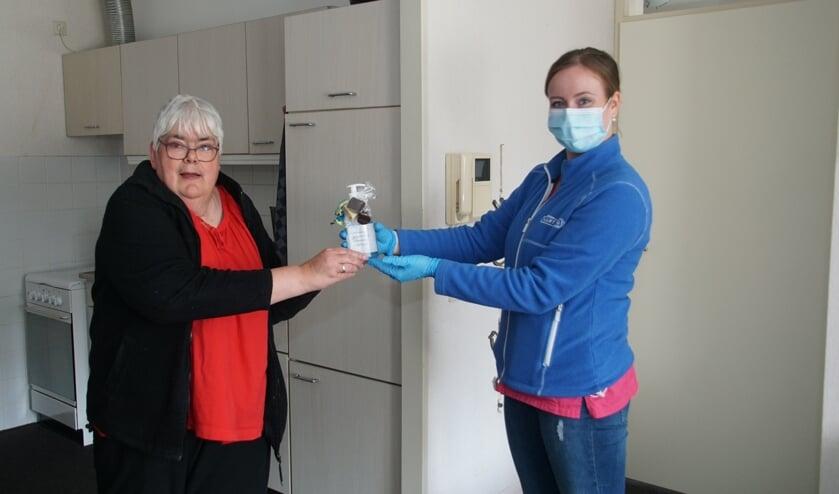 Buurtzorg-medewerker Kim Smits overhandigt de attentie aan cliënte Wilma Oonk. Foto: Frank Vinkenvleugel