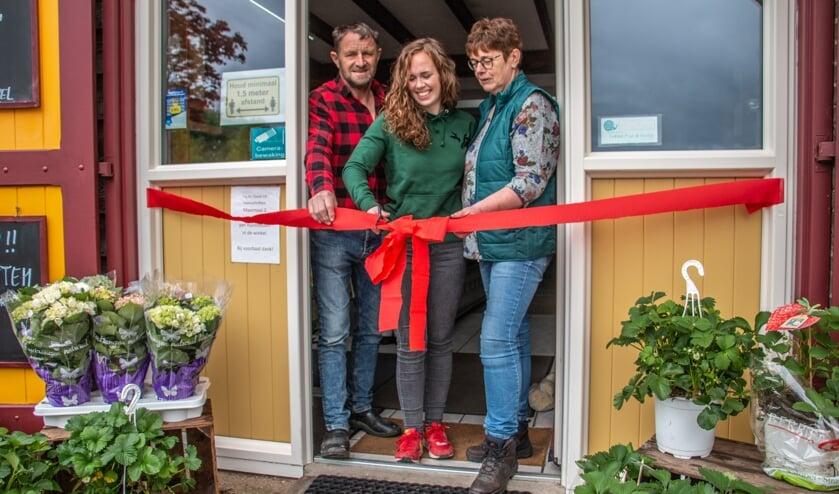 Dick, Iris en Jolanda Garritsen knippen het lint door van de verbouwde winkel. Foto: Liesbeth Spaansen