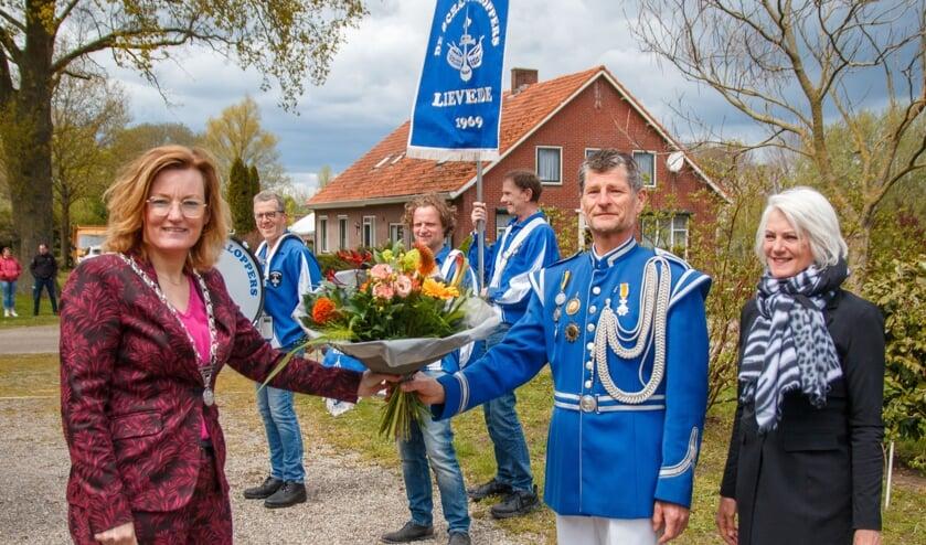 Locoburgemeester Marieke Frank reikt een koninklijke onderscheiding en bloemen uit aan Broddy Krabbenborg. Rechts zijn vrouw, Nardy Krabbenborg. Foto: PR