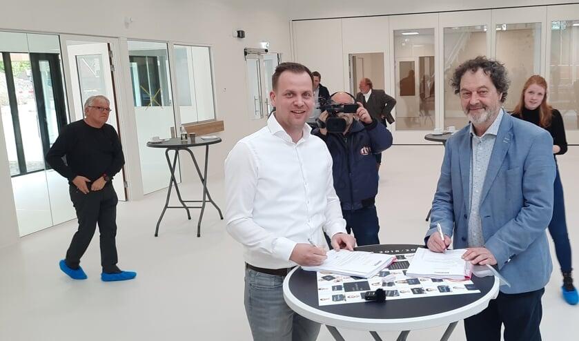 <p>Bart Wopereis van Binx Smartility (links) en Hans Reede van het IEKC ondertekenen de officiële overdrachtspapieren. Foto: Kyra Broshuis</p>