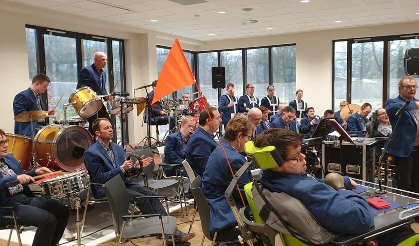 <p>Tonnie Weikamp staand te midden van muzikanten van de Rainbowband tijdens een optreden bij Zozijn in Wilp. Foto: eigen foto.</p>