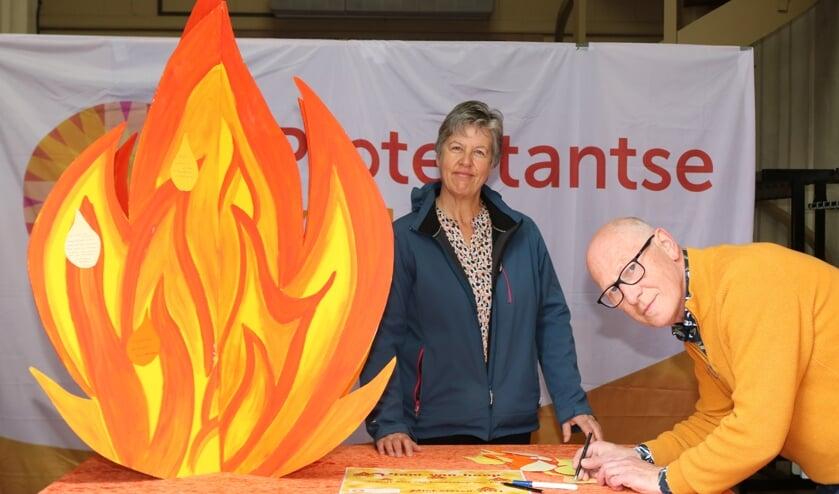 <p>Janny Gerritsen bij de Vlam van Hoop terwijl Sander van Voorst een tekstballon beschrijft. Foto: Arjen Dieperink</p>