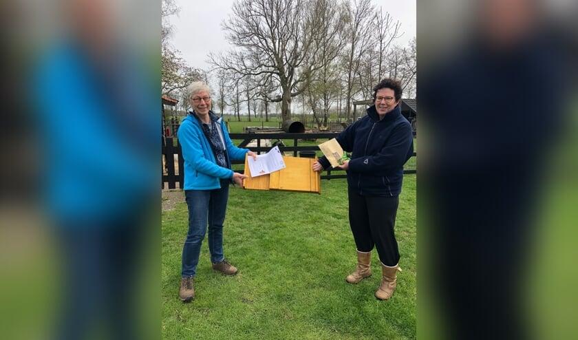<p>WBH-vrijwilliger Marleen van der Linde (l.) levert bij deelnemer Sandra ter Maat het zaaigoed en de vleermuiskast af. Foto: Marja Polman</p>
