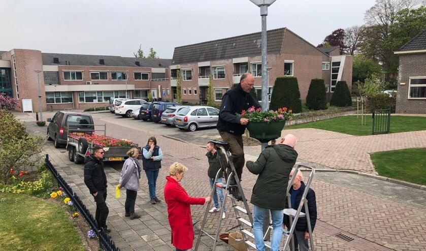 <p>Vrijwilligers gaan de trapjes op om de bloembakken te bevestigen. Foto: Geert Postma</p>