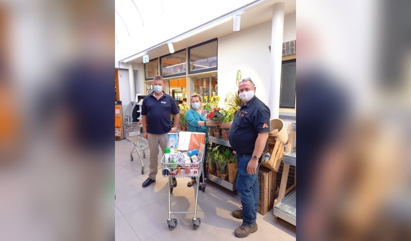 Erik en Loes Jansen uit Drempt wonnen de minuut winkelen. Harold Aalderink reikte na afloop bloemen uit. Foto: Coop Steenderen