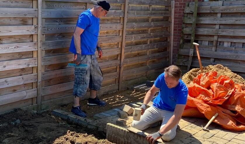 <p>Twee collega&#39;s van Iets Anders Makelaars zijn bezig met het afmaken van het terras in de achtertuin. Foto: pr Present Aalten-Dinxperlo&nbsp;</p>