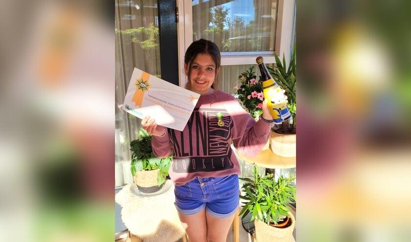 <p>De trotse Jannah met de opgespelde medaille, onderscheiding en fles kinderchampagne. Foto: PR</p>