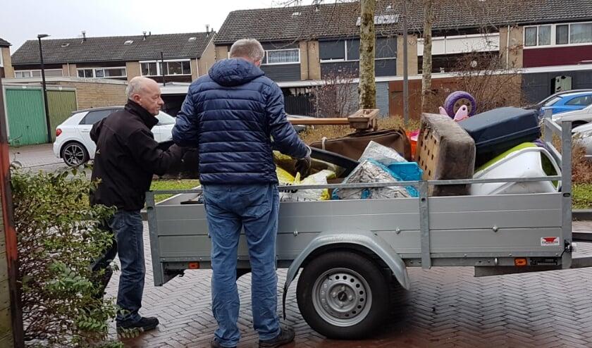 <p>Twee vrijwilligers laden een aanhangwagen vol tijdens een opruimklus. Foto: Present Winterswijk</p>