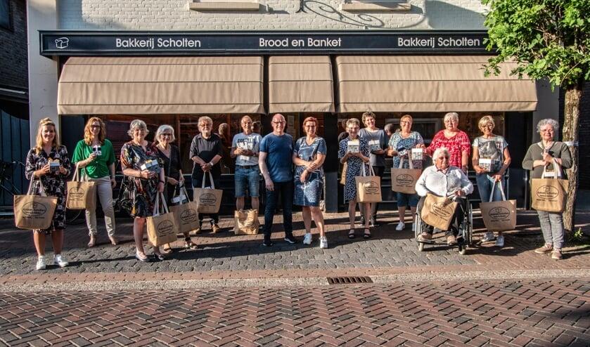 <p>Henry en Sandra van bakkerij Scholten (m.) met alle prijswinnaars van de jubileumactie. Foto: Liesbeth Spaansen</p>