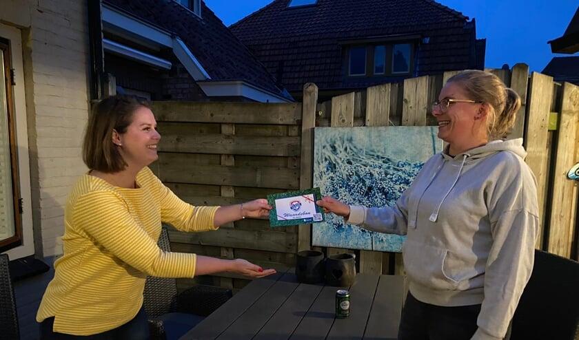 DEO bestuurslid Mieke Kornegoor (links) overhandigt de waardebon aan DEO voetbaldame Kim Veneklaas. Foto: PR DEO
