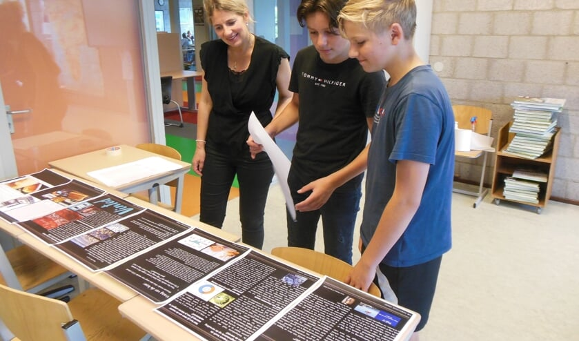 <p>Docent Iris Rozemuller bekijkt met twee leerlingen een van de kranten. Foto: Eric Klop</p>