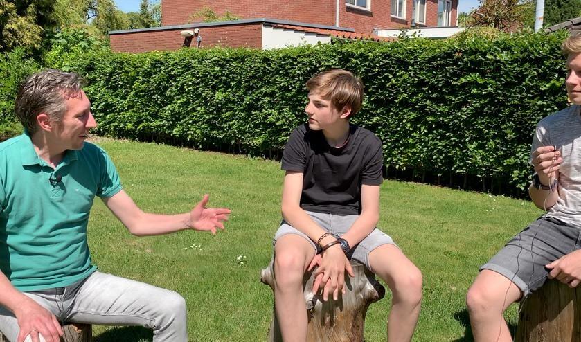 Sander Ris (links) in gesprek met Joran en Janiek (rechts) bij het Dorpshoes in Gelselaar. Foto: PR