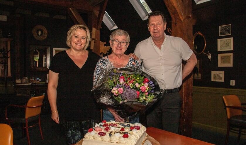 <p>Ans Mulder (m) krijgt van Odeke Brinkhorst en Herman Meutstege alvast een taart en bloemen voor haar pensioen, na 46 jaar Het Wapen van Bronkhorst. Foto: Liesbeth Spaansen</p>