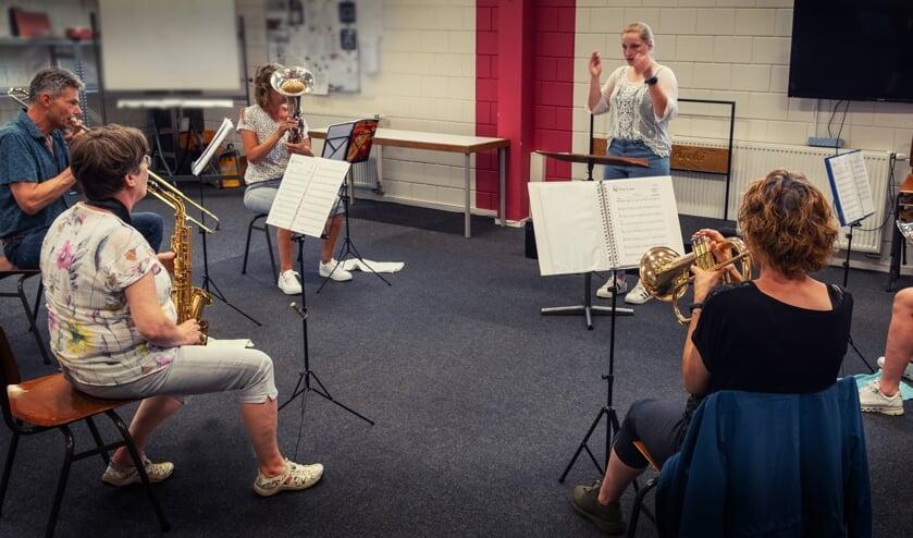 Docent Dorien Jansen Venneboer aan de slag met een aantal muzikanten uit de orkestklas.