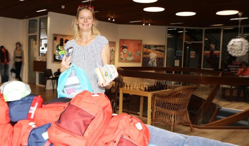 <p>Voorzitter Hellen Strik toont de inhoud van &eacute;&eacute;n van de tassen. Foto: Arjen Dieperink</p>