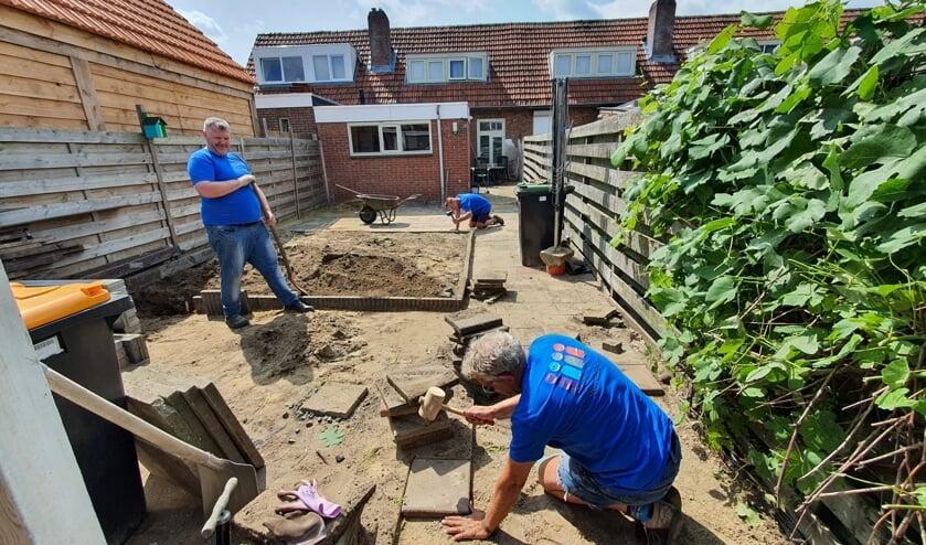 <p>De vrijwilligers zijn druk bezig met het bestraten van de achtertuin. Foto: Present Aalten Dinxperlo</p>