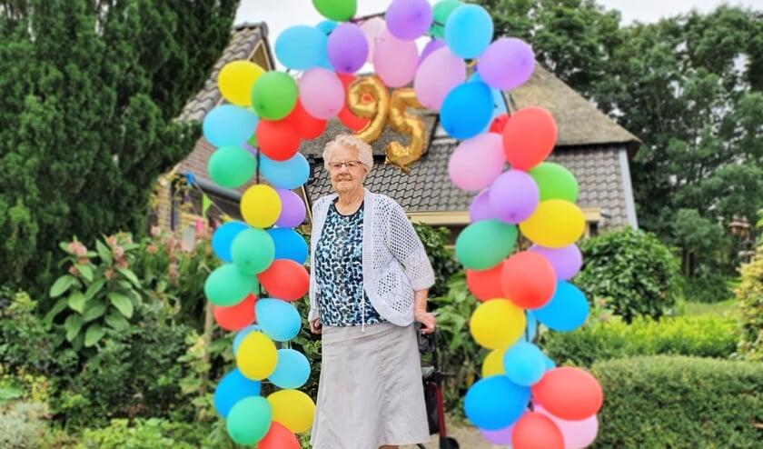 <p>Op de verjaardagstaart van Gerda Gaijkhorst-Kornegoor stonden op maandag 19 juli vijfennegentig kaarsjes. De buurt zette haar in het zonnetje met een ballonenboog. Foto: Alice Rouwhorst</p>