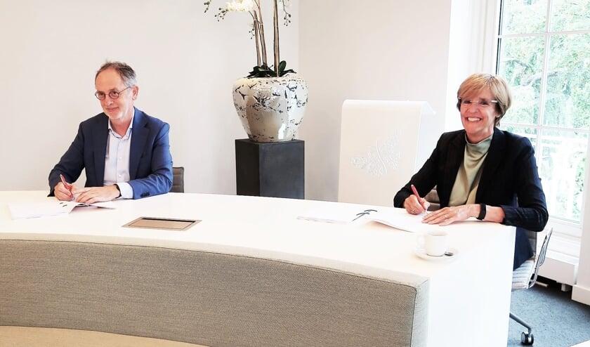 Burgemeester Annette Bronsvoort en bestuurder Ad Smeets ondertekenen de intentieovereenkomst. Foto: Theo Huijskes.