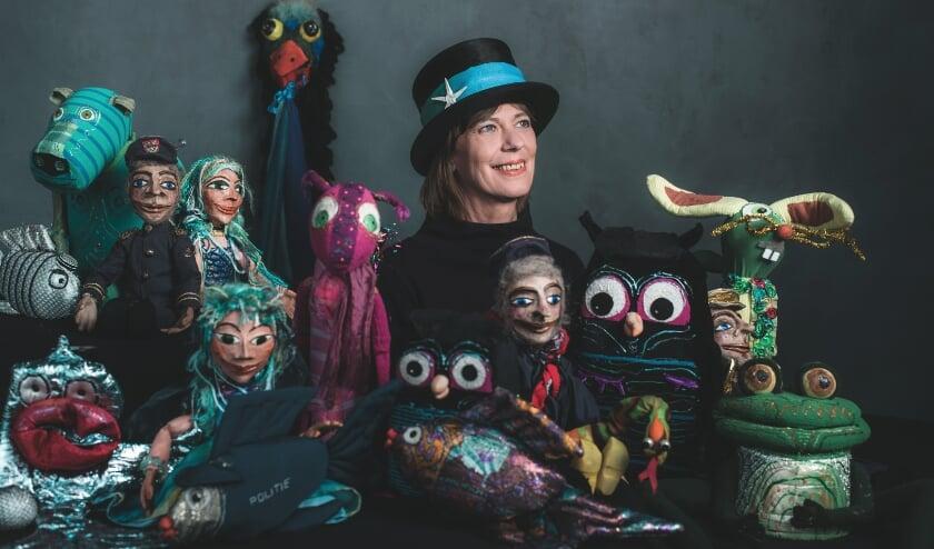 <p>Arida tussen haar poppen uit de voorstellingen &lsquo;Kapitein Jan en het geheim van de zoute zee&rsquo; en &lsquo;Oehoe&rsquo; (Mama kwijt). Op de achtergrond staat haar &lsquo;verhalenpaal&rsquo;.&nbsp;</p><p>Foto: Ysbrand Cosijn &ndash; Studio Ysbrand</p>