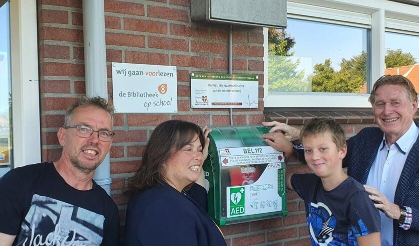 Wethouder Elvira Schepers (links) stelt samen met Bart Jan de buurt-AED in het Woold officieel in werking. Links van haar René Walvoort en uiterst rechts Johan G. Esendam. Foto: PR