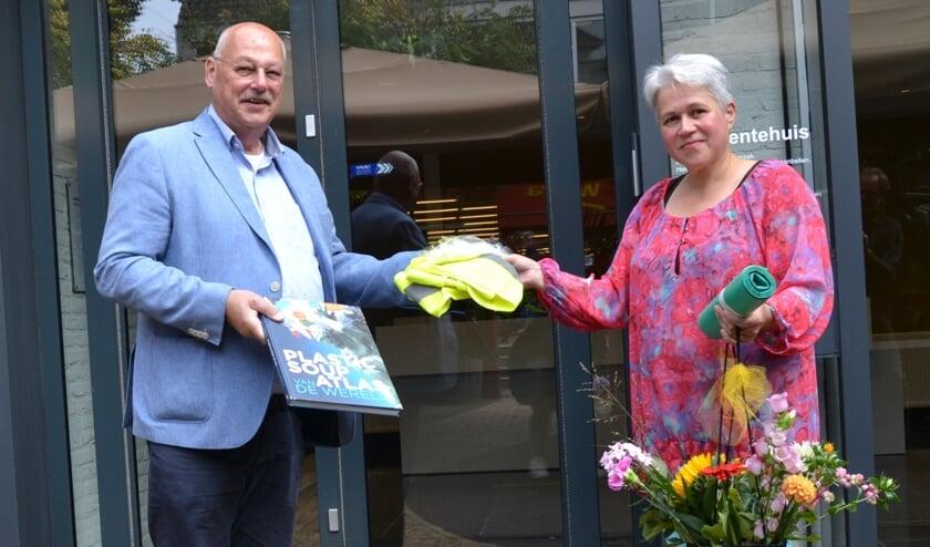 <p>Anke Colenbrander neemt nieuwe hesjes, een boek en bloemen aan van wethouder Martin Veldhuizen. Foto: Karin Stronks</p>