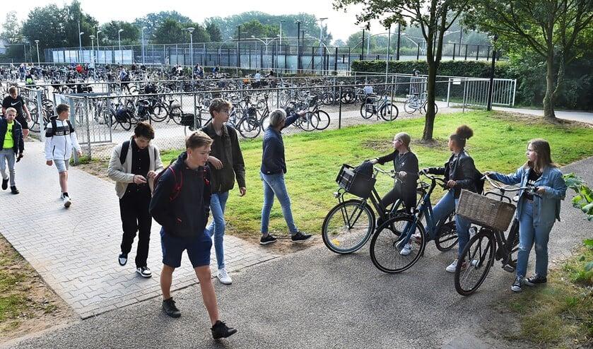 <p>Conciërge Isala Yvonne Mijnen wijst de leerlingen de ingang van de fietsenstalling bij Laudis en Almende College. Foto: Roel Kleinpenning</p>