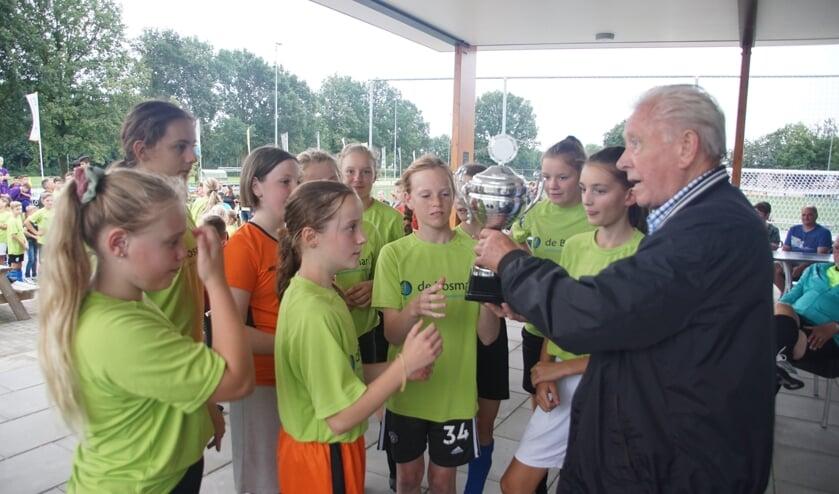 <p>Het winnende meisjesteam Bosmark A krijgen de beker uit handen van Willy te Grotenhuis. Foto: Frank Vinkenvleugel</p>