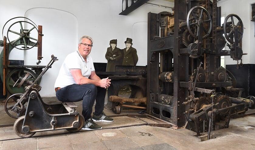 Ludo Schenning bij de 'Krupp' raamzaagmachine uit 1905, op de achtergrond een foto van Lena en Theodor Damen, de opa en oma van Ludo. Foto: Roel Kleinpenning