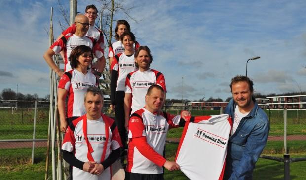 Jan Schoorl van Stichting Kees overhandigt de opvallende hardloopshirts aan de deelnemers van Running Blind.