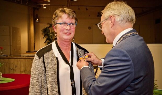 De burgemeester spelt de onderscheiding bij Marry van Dijk op. Foto: Stip Fotografie