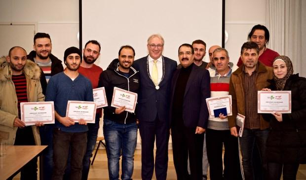 De statushouders met burgemeester Romeyn in het midden. Rechts van de burgemeester de heer Aziz Azizi, hij heeft dit project ontwikkeld. Foto: Stip Fotografie