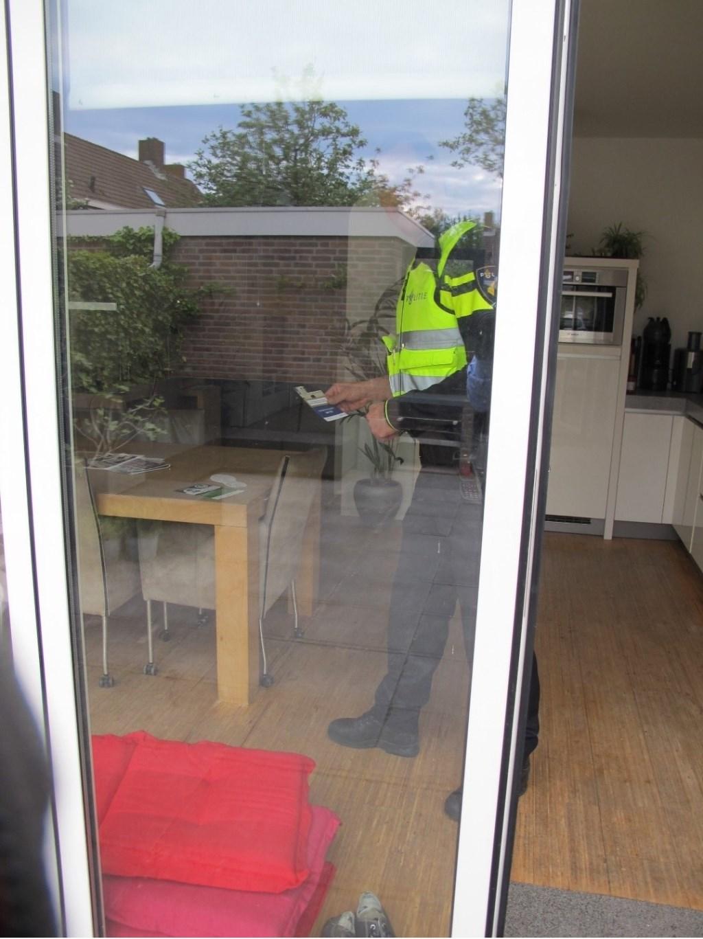 Een politieagent legt een 'witte voetjes'-brochure in een woning waarvan de deur openstond. Bron: www.buurtpreventieheiloo.nl  © Uitkijkpost Media B.v.