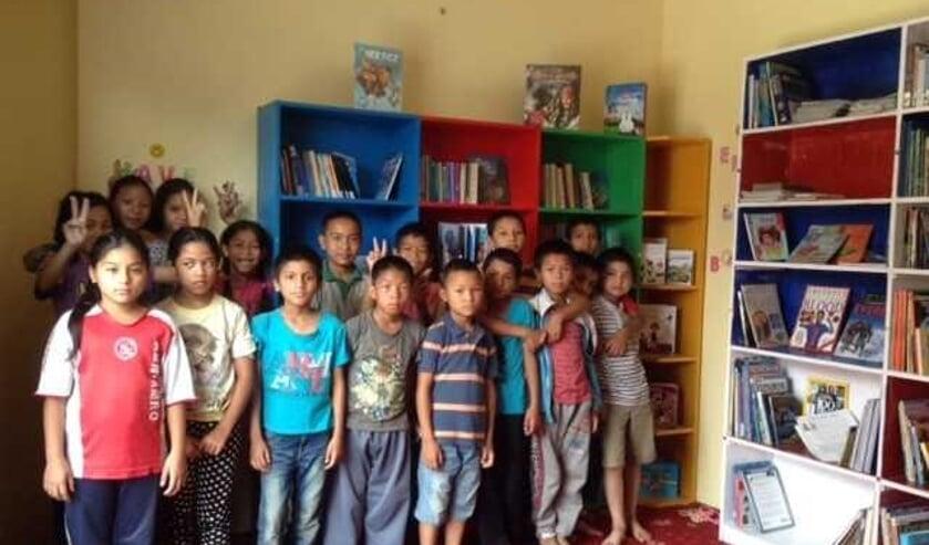 De Nepalese kinderen in de blbliotheek van het tehuis