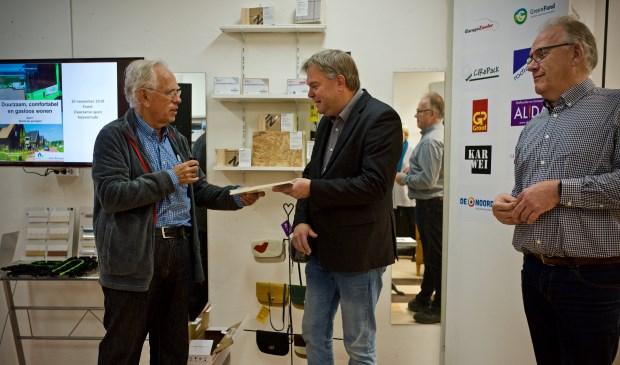 Wethouder Rob Opdam ontvangt uit handen van Harm Hofman het boekje 'Duurzaam comfortabel gasloos wonen', Geheel rechts Rob  van der Wal.