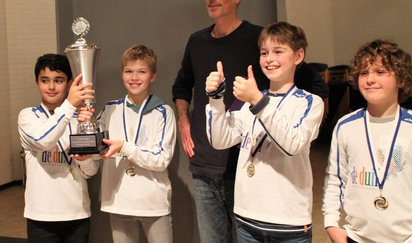 Schaakteam De Duif 1 (v.l.n.r. Darien, Quinten, Jasper en Sil) onder leiding van 'schaakvader' Asaf Lahat won de wisselbeker op het Schoolschaaktoernooi van SV Oppositie.