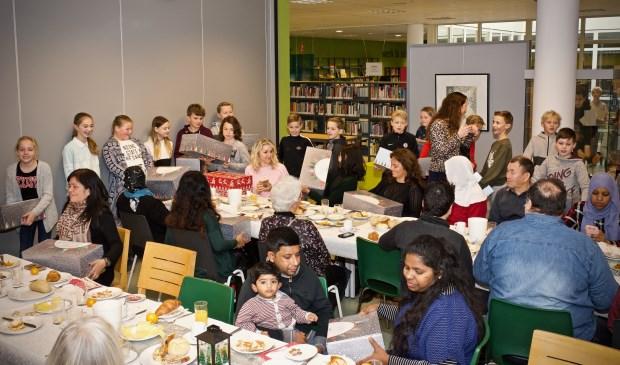 Leerlingen van de groepen 7 en 8 delen de eigengemaakte kerstpakketten uit.