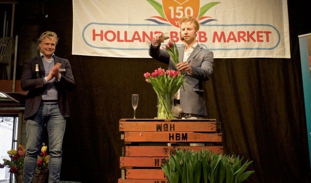Directeur Joris van der Velden kijkt toe hoe illusionist Steve Carlin een naar hem genoemde tulp doopt.