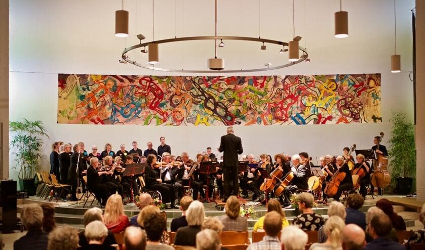 Het Arnhems Symfonie Orkest NOVA en het Peace Opus koor onder het kunstwerk van Annemarie Kuster.